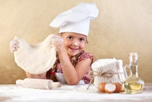 Little girl making pizza dough