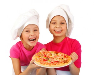 Two happy girls preparing pizza